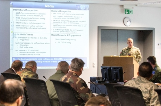 The audience listens as Wing Commander Carl Jeffrey (behind podium) give a situation briefing to the participants of TRIDENT JET during the rehearsal session on Dec. 1. Photo by Cynthia Vernat, HQ AIRCOM Public Affairs.